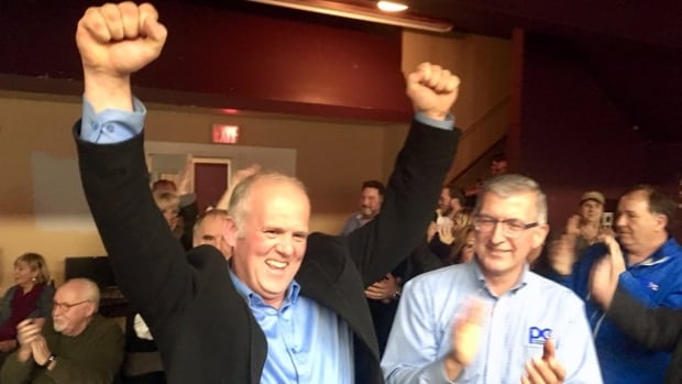 Jim Lester raises his hands in the air alongside PC leader Paul Davis on Tuesday evening at his campaign headquarters in Mount Pearl.
