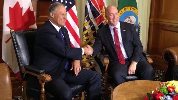B.C. Premier John Horgan, right, shakes hands with Washington State Gov. Jay Inslee as the two meet at the legislature in Victoria on Tuesday.