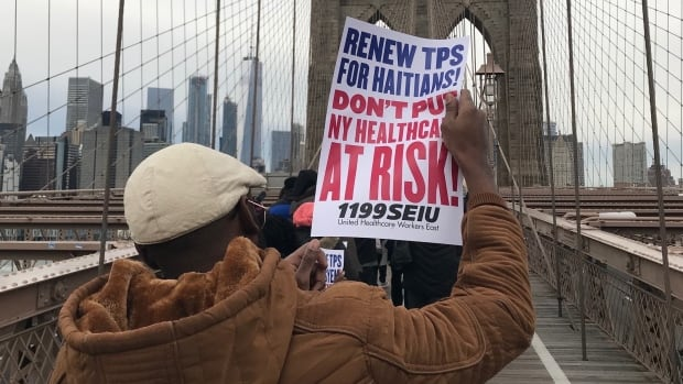 A protester holds a sign calling for the renewal of Temporary Protected Status during a march across the Brooklyn Bridge on Saturday, Nov. 18.