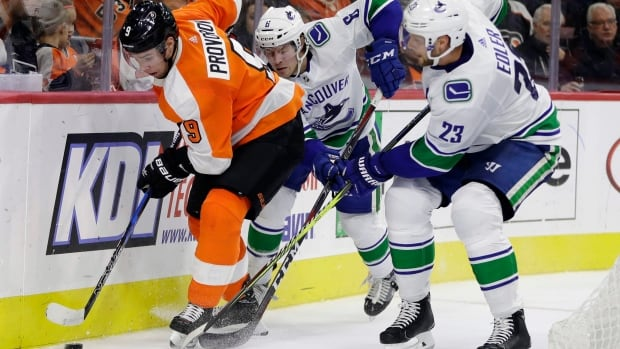 Philadelphia Flyers' Ivan Provorov (9) tries to keep the puck away from Vancouver's Brock Boeser (6) and Alexander Edler (23) during the Canucks' 5-2 win on Tuesday.