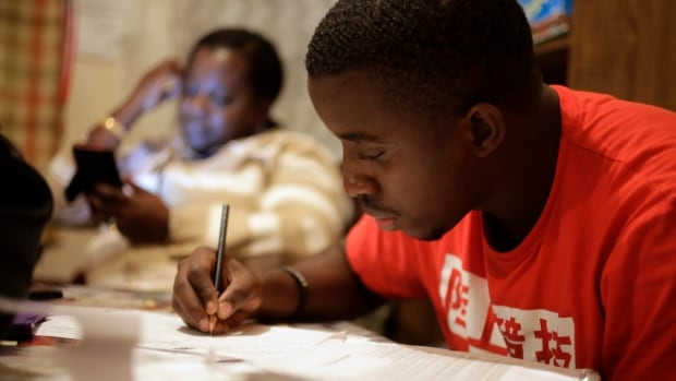 Amocachy Jeune, right, does homework as his mother Marianne Jeune, left, a Haitian immigrant staying in the U.S. through the Temporary Protected Status program, sits nearby at their Boston home. Washington said this week it will end the program for Haitians.