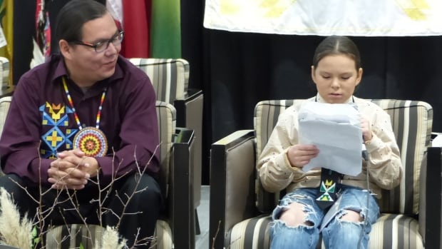 Robert (JR) McArthur sits with his nephew Bronte Big Eagle as he reads his story to a packed house at the First Nations Language Keepers Conference in Saskatoon.