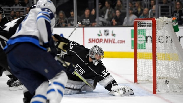 Adam Lowry, left, of the Jets scores on Kings' goalie Jonathan Quick during Winnipeg's 2-1 win on Wednesday, in Los Angeles, Calif.