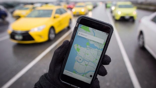 The Uber app is displayed on an iPhone as taxi drivers wait for passengers at Vancouver International Airport, in Richmond, B.C. Although ride-hailing services are not yet allowed in B.C., at least seven different ones operate in the area.