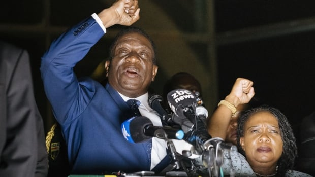 Zimbabwe's incoming president Emmerson Mnangagwa, left, speaks to supporters flanked by his wife Auxilia at the ruling Zanu-PF party headquarters in Harare on Wednesday.