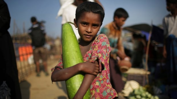 """A Rohingya Muslim girl carries a vegetable from the market on the outskirts of Kutupalong refugee camp on Tuesday, Nov. 21, 2017, in Bangladesh. Since late August, more than 620,000 Rohingya have fled Myanmar's Rakhine state into neighboring Bangladesh, seeking safety from what the military described as """"clearance operations."""""""