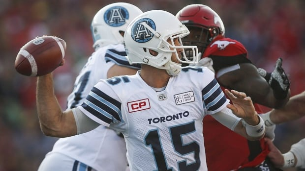 Toronto Argonauts' quarterback Ricky Ray throws the ball as a Calgary Stampeders closes in during first half CFL football action in Calgary, Saturday, Aug. 26, 2017. THE CANADIAN PRESS/Jeff McIntosh
