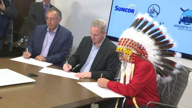 Fort McKay First Nation Chief Jim Boucher, left, Mark Little, Suncor's president of upstream operations, and Mikisew Cree First Nation Chief Archie Waquan finalize the $503 million acquisition of interest in a Suncor oilsands project.