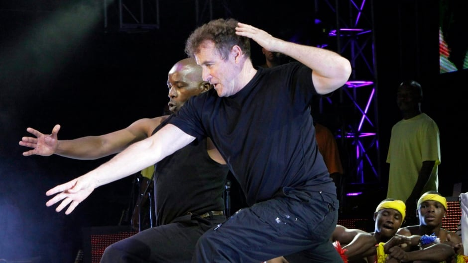 South African musician Johnny Clegg performs a dance routine during a 2010 concert in Johannesburg. Clegg, who blended Western pop and Zulu rhythms in multi-racial bands during white minority rule, is in the midst of his final tour. He was diagnosed with pancreatic cancer in 2015.