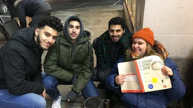 From left, Omar Ali, Mohammed Baba, Saul Delgado and Sarah Chaput wait outside the H&M Ste-Catherine and Peel streets to take advantage of Black Friday deals.