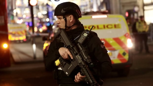An armed police officer stands guard on Oxford Street in London on Friday.