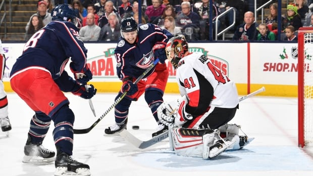 Cam Atkinson, centre, of the Blue Jackets takes a shot on goaltender Craig Anderson of the Ottawa Senators during Columbus' 5-2 win on Friday.