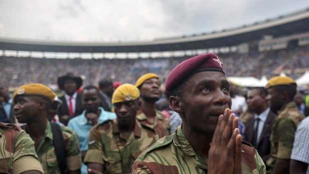 A soldier watches Zimbabwe President Emmerson Mnangagwa's speech on a large screen inside the National Sports stadium in Harare during the presidential inauguration ceremony on Friday.