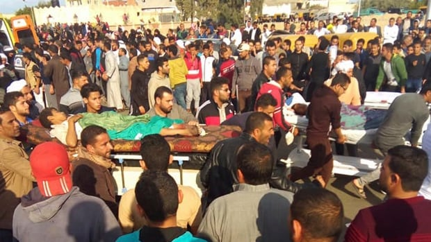 Injured people are transported from the scene of Friday's attack in Bir al-Abd. More than 300 people were killed before the assailants got away.