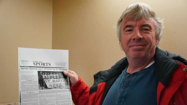 Pat Payton holds up the sports section of the St Marys Journal Argus, which will shut down after 160 years of operation because of a deal between media giants Torstar and Postmedia.