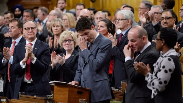 Prime Minister Justin Trudeau wipes his eye while he is applauded as he delivers a formal apology to LGBT people in Canada in the House of Commons in Ottawa, Tuesday, Nov.28, 2017.