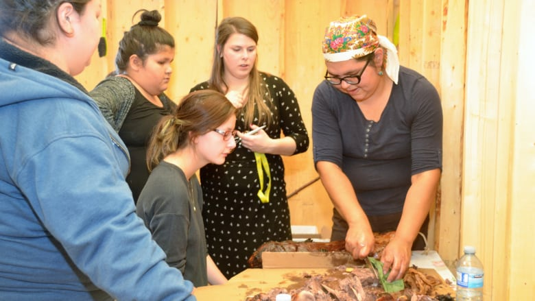 Flora Otter demonstrates how to prepare a beaver, at the Cree Culture  teaching site that opened last month in Waswanipi, Que. (Cree School Board)