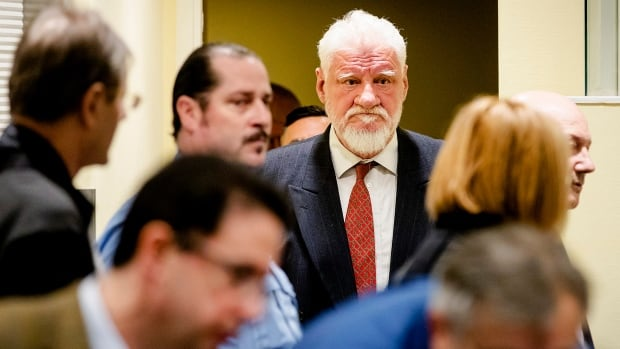 Praljak, centre, enters the tribunal on Wednesday. His lawyer called for a doctor, saying her client had claimed to drink poison while his verdict was being read. He later died.