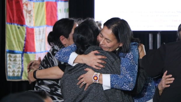 Commissioner Michèle Audette hugs families from Unamen Shipu, Que., who gave devastating testimonies at the MMIWG inquiry on Wednesday in Mani-Utenam.