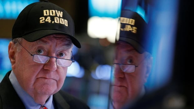 Art Cashin, director of floor operations at UBS, wears a Dow 24,000 hat as he works on the floor of the New York Stock Exchange on Thursday, as the Dow Jones Industrial Average crossed 24,000 for the first time.