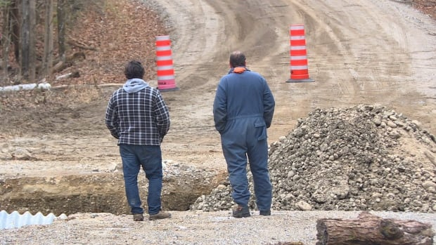 Two men examine temporary repairs by neighbours on Paugan Road. The municipality put a stop to the work.