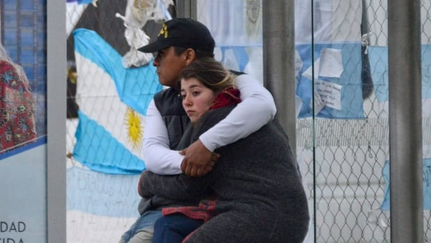 Relatives of crew members from the missing ARA San Juan submarine hug outside the navy base in Mar del Plata, Argentina, Thursday, after the navy said it was stopping rescue efforts.