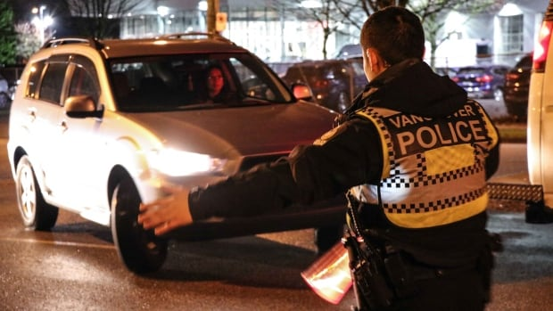 A Vancouver police officer pulls over a car at a drinking and driving CounterAttack checkpoint on Dec. 1, 2017.