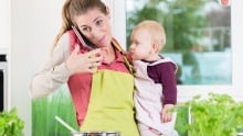 Shutterstock mom cooking on phone with baby