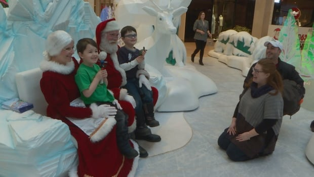 Zach Belisle and his brother Luke visit with Santa and Mrs. Claus
