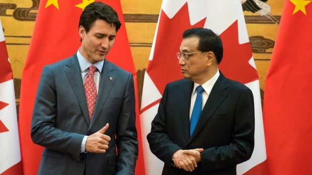 Canadian Prime Minister Justin Trudeau, left, and Chinese Premier Li Keqiang speak during a signing ceremony at the Great Hall of the People in Beijing Monday, Dec. 4, 2017.
