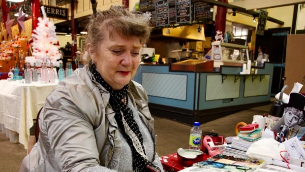Linda Cooke was dressed in silver Monday to mark 25 years of painting Saint John scenes in the City Market.