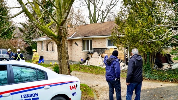 Investigators assess the aftermath of a house explosion on Hamilton Road Monday afternoon.