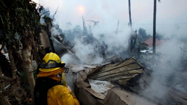 A firefighter hoses down smouldering debris in Ventura Calif. on Tuesday. Ferocious Santa Ana winds raking Southern California whipped explosive wildfires Tuesday prompting evacuation orders for thousands of homes