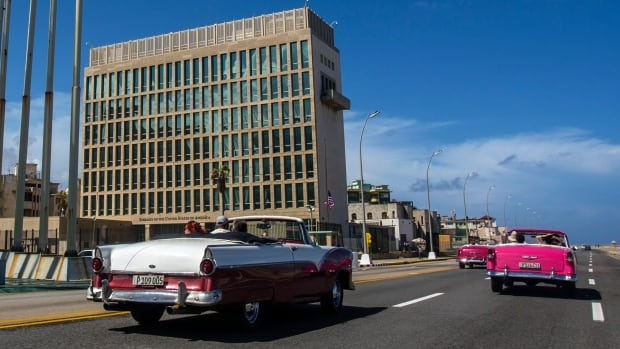 Tourists ride classic convertible cars on the Malecon beside the United States Embassy in Havana, Cuba. Doctors treating the U.S. Embassy victims of mysterious, invisible attacks in Cuba have discovered brain abnormalities as they search for clues to hearing, vision, balance and memory damage, The Associated Press has learned.