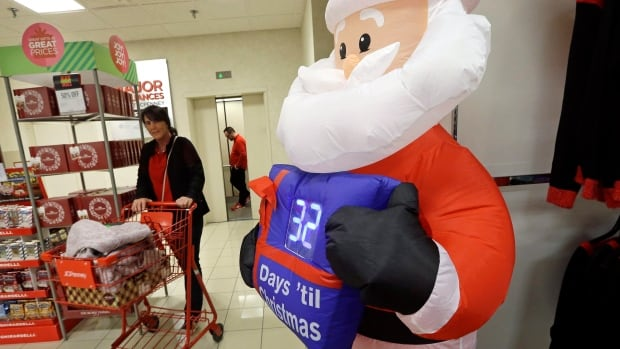 A shopper rolls a full cart past a Santa figure with a countdown clock numbering the days until Christmas. Respondents to a CIBC survey said they felt pressure to buy gifts and more than half expect to spend more than they want.