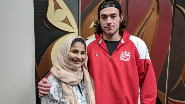 Noor Fadel standing with Jake Taylor, the only passenger to intervene and help her.