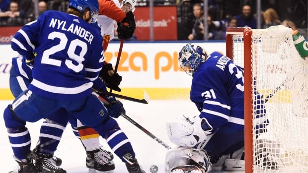 Calgary Flames centre Sean Monahan (23) tries to get the puck past Toronto Maple Leafs goalie Frederik Andersen (31) as Maple Leafs centre William Nylander (29) defends.