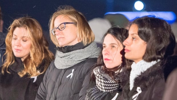 Sophie Grégoire Trudeau, left, Catherine Bergeron, sister of Genevieve who was killed in the attack, Montreal Mayor Valérie Plante and Quebec Deputy Premier Dominique Anglade, right, take part in a ceremony marking the 28th anniversary of the Polytechnique shooting.