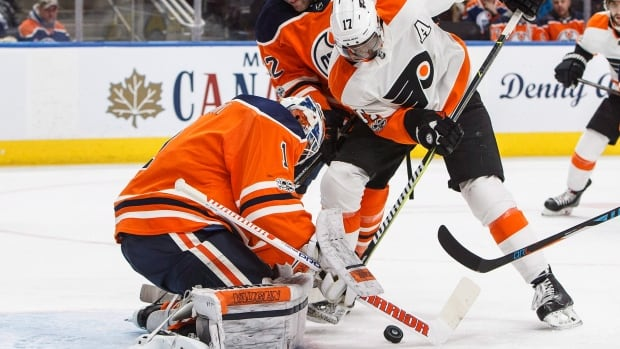 Philadelphia Flyers' Wayne Simmonds is stopped by Edmonton Oilers' goalie Laurent Brossoit as Eric Gryba (62) defends during first period at Rogers Place on Wednesday.