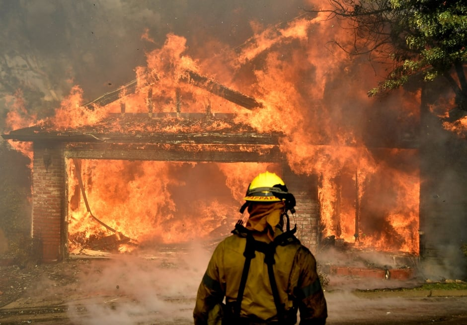 USA California WILDFIRES firefighter battles burning home