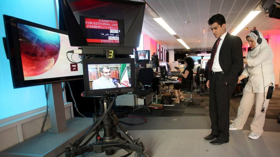 BBC Persian service presenter Fardad Farahzad, right, gets ready to present the news at the corporation's London headquarters. The BBC says it has filed a complaint with the United Nations over Iran freezing the assets of over 150 people associated with its Persian service.