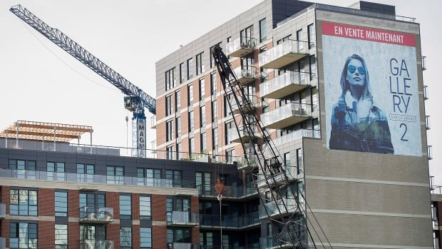Cranes are shown next to a sign advertising property on the side of a new housing development in Griffintown last month. A bump condo sales has lead to the best November for real estate in eight years.