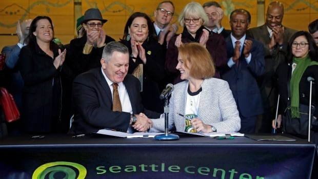 Seattle Mayor Jenny Durkan, right, shakes hands with Oak View Group CEO Tim Leiweke after they signed an agreement to renovate KeyArena. On Thursday, the NHL agreed to accept an expansion application from the city.