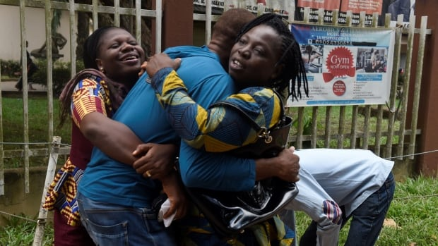 A returnee migrant, centre, brought home from Libya is embraced by relatives in Benin, the capital of Edo State in midwest Nigeria, on Thursday.