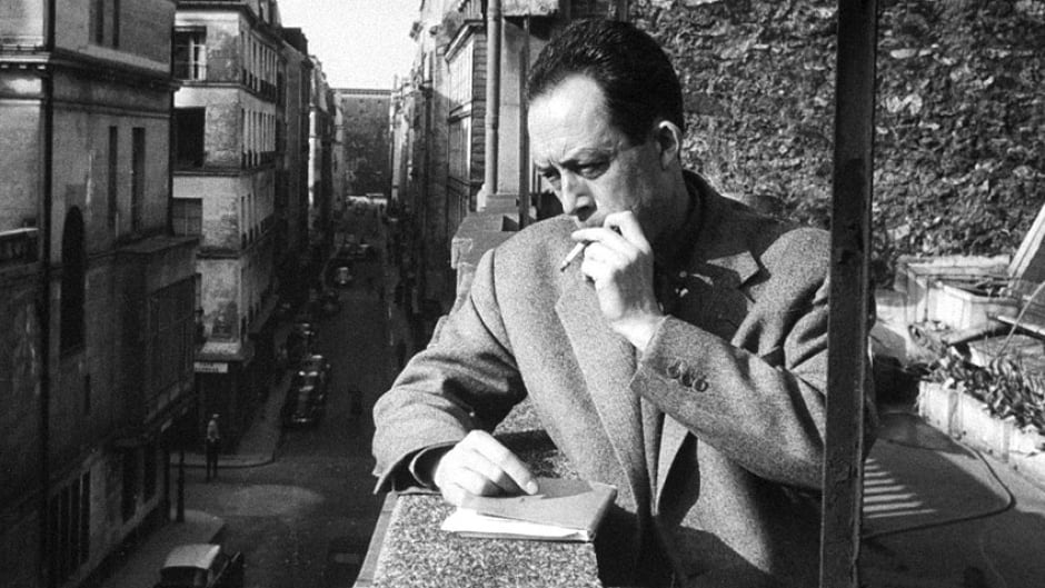 Albert Camus smoking cigarette on balcony outside his publishing firm office, 1955.
