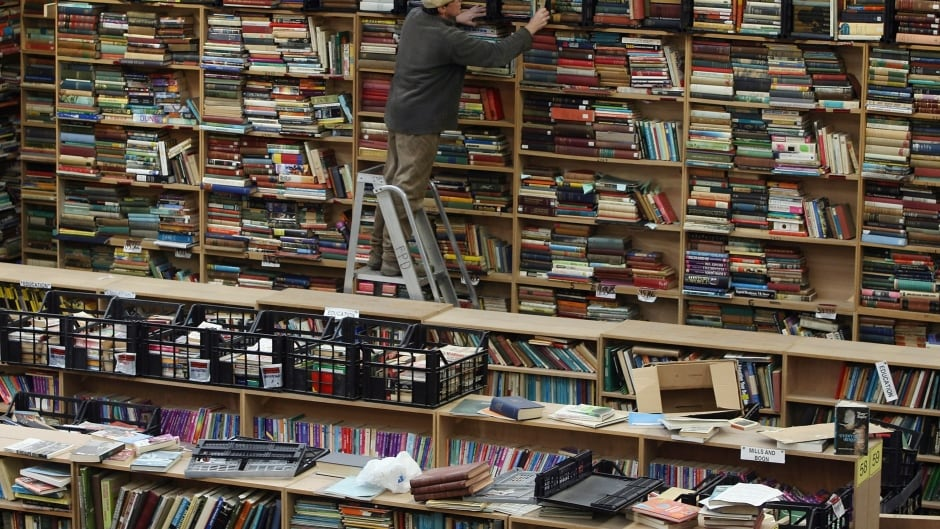 An employee searches the shelves at Bookbarn International in Somerset, England.