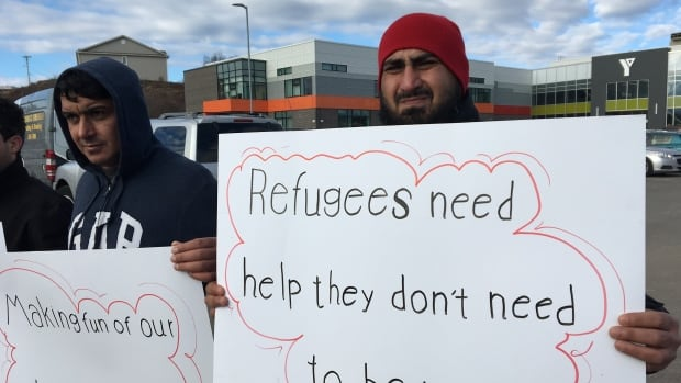Ali Abed, right, joined several other Syrian refugees outside the YMCA of Greater Saint John on Friday to share concerns about a lack of qualified interpreters.