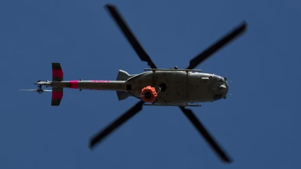 A U.S. military helicopter makes a water drop on a hotspot caused by the Lilac Fire, a fast-moving wildfire in Bonsall, Calif., on Friday.