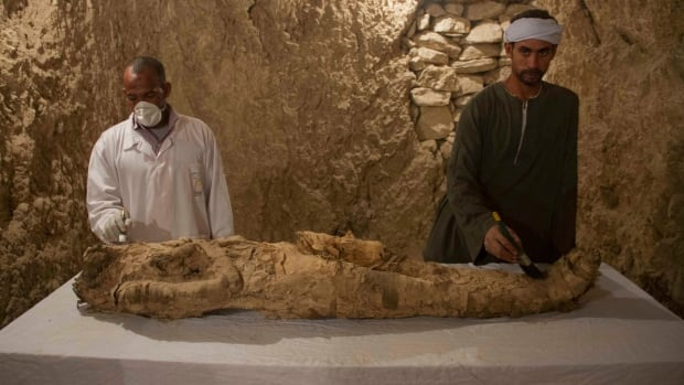 Egyptian excavation workers restore a mummy in a newly discovered tomb on Luxor's West Bank.