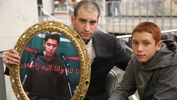 Human rights activist Firas Al Najim, centre, and Yosif Al-Hasnawi's younger brother Ahmed Al-Hasnawi hold a photo of Yosif Al-Hasnawi at Saturday's memorial at Hamilton city hall.